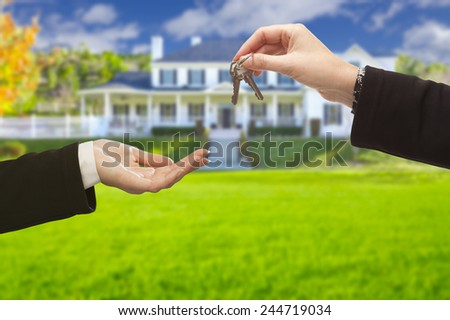Real Estate Agent Handing Over the House Keys in Front of a Beautiful New Home. - stock photo
