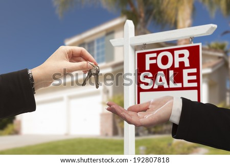 Real Estate Agent Handing Over the House Keys in Front of a Beautiful New Home and For Sale Real Estate Sign.