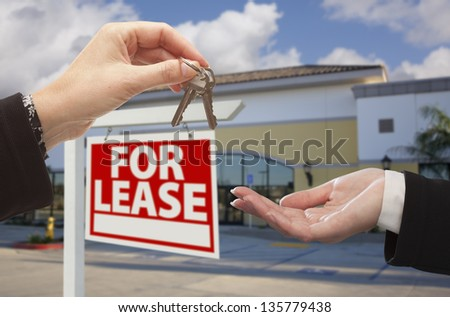 Real Estate Agent Handing Over the Keys in Front of Vacant Business Office and For Lease Sign. - stock photo