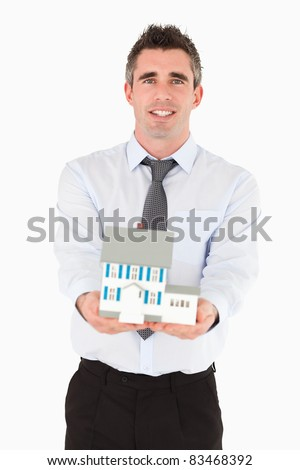 Real estate agent holding a miniature house against a white background - stock photo