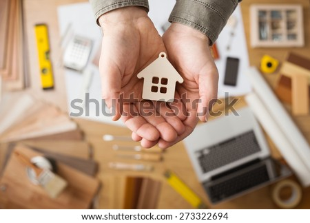 Real estate agent holding a small house, desktop with tools, wood swatches and computer on background, top view - stock photo