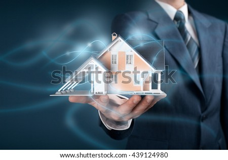 Real estate agent offer intelligent house, smart home and home automation concept. Model of the house and wireless communication with intelligent house represented by futuristic graphics.