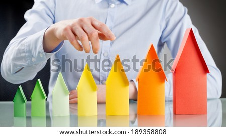 Real estate agent or a home buyer selecting an energy efficient house from a row of paper houses in energy label colors. - stock photo