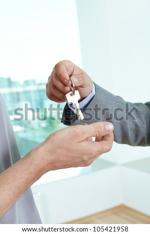Real estate agent passing the key to the house to a satisfied male homeowner - stock photo