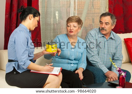 Real estate agent presenting a minaiture house to mature couple in their house - stock photo