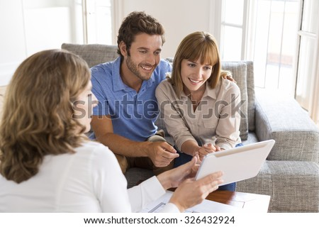 Real-estate agent presenting a new project property on digital tablet - stock photo