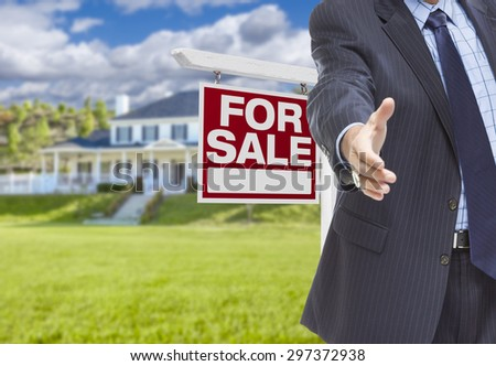 Real Estate Agent Reaches for Handshake with Sale Sign and New House Behind. - stock photo