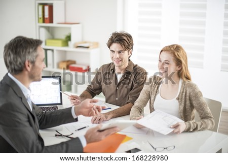 real-estate agent receives a young couple interested to invest in an house - stock photo