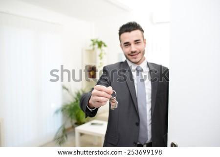 real estate agent salesman handing over house keys  - stock photo