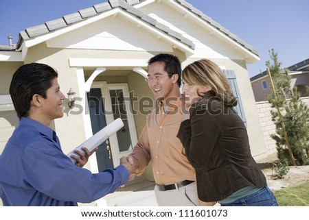 Real estate agent shaking hand with couple buying new house
