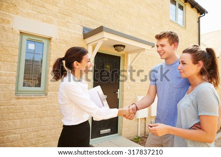 Real estate agent shaking hands with new property owners - stock photo