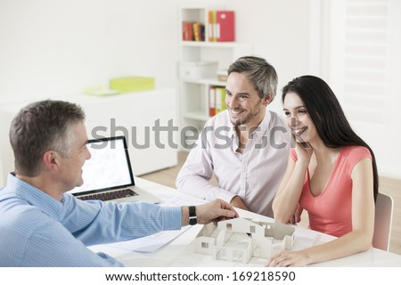 real estate agent showing a construction project to a couple - stock photo