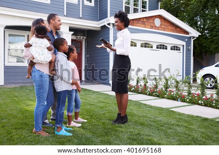 Real estate agent showing a family a house - stock photo