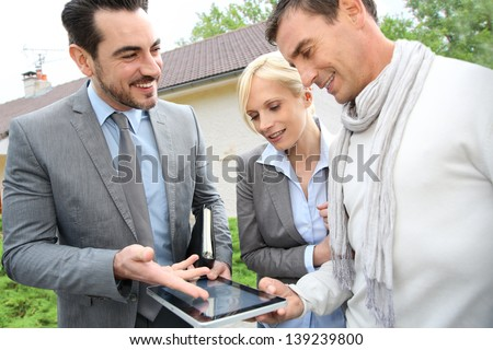 Real-estate-agent showing house plan on digital tablet - stock photo