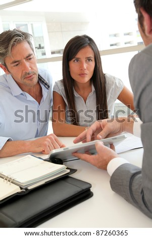 Real-estate agent showing house plans on electronic tablet - stock photo