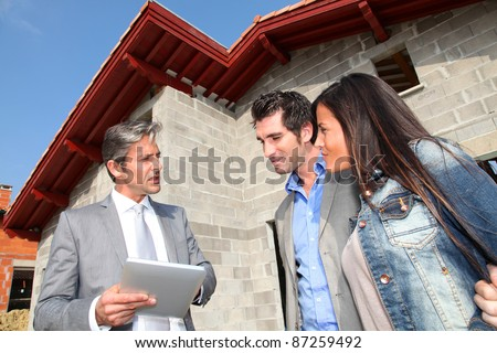 Real-estate agent showing house under construction to couple - stock photo