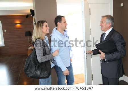 Real estate agent showing modern house to couple - stock photo