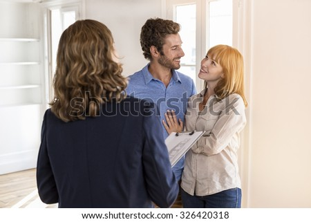 Real estate agent showing modern white apartment to futur owners couple - stock photo