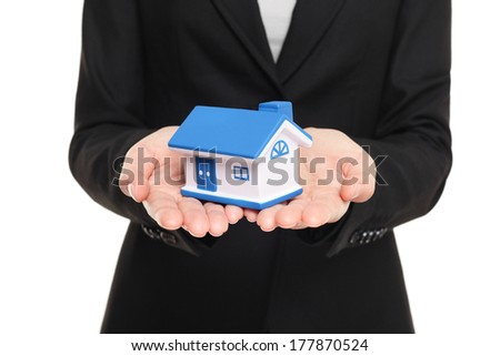 Real estate agent showing new house in mini size. New home owner concept. Realtor showing holding house model. Buying new home conceptual image with business woman in suit isolated on white background - stock photo