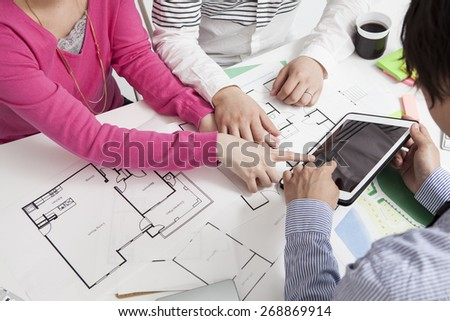 Real-estate agent shows a build project on a digital tablet to a young couple - stock photo