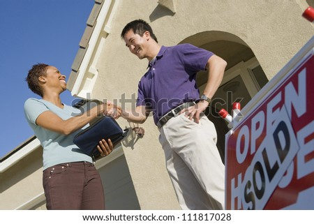 Real estate agent with asian man buying new house - stock photo