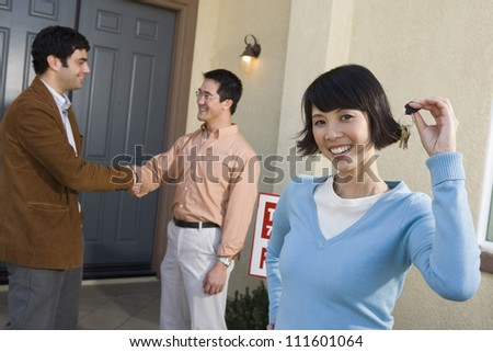 Real estate agent with cheerful asian couple buying new house - stock photo
