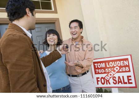Real estate agent with cheerful couple buying new house - stock photo