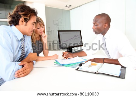 Real-estate agent with couple in office - stock photo