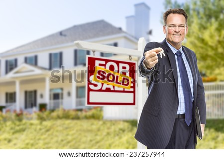 Real Estate Agent with House Keys in Front of Sold Sign and Home. - stock photo
