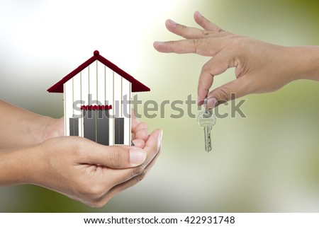 Real estate agent with house model and keys on green backgrounds - stock photo