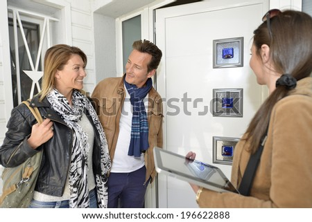 Real-estate agent with tablet showing house to clients - stock photo