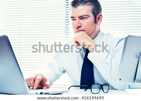 Real estate agent working on his laptop, looking for the perfect home for his clients.   Business, mortgage, brokerage, corporate and career concept - stock photo