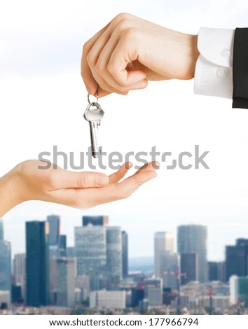real estate and banking concept - close up of man hand passing house keys to woman - stock photo