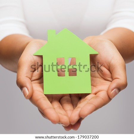 real estate and eco concept - closeup picture of woman hands holding green house - stock photo