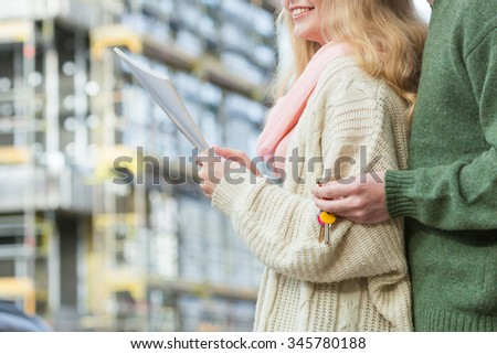 Real estate and family concept - young couple on front of new big modern house construction site with blueprint project keys dreaming about home - stock photo