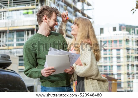 Real estate and family concept - young couple on front of new big modern house construction site with blueprint project keys dreaming about home