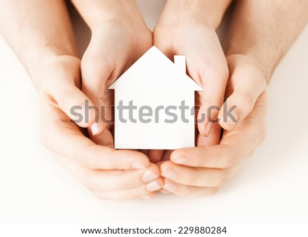 real estate and family home concept - closeup picture of male and female hands holding white blank paper house - stock photo