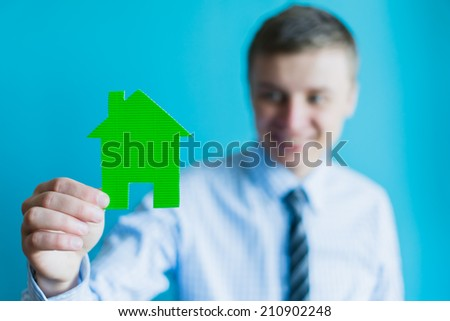 real estate and family home concept - closeup picture of male hand holding green paper house
