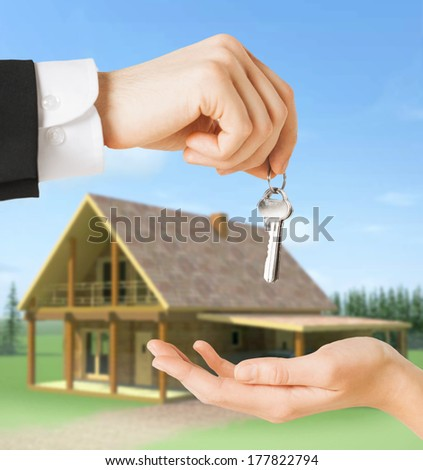real estate and home concept - close up of man hand passing house keys to woman