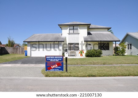 Real estate (another success let us help you buy sell your next home) sign on front yard lawn of suburban home residential neighborhood USA clear blue sky