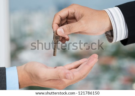 Real estate broker giving the key to the client - stock photo