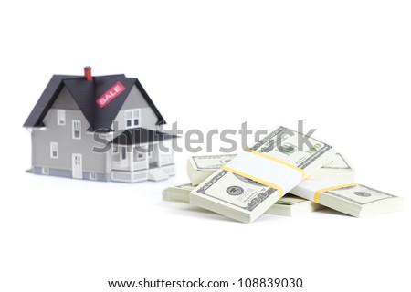 Real estate concept - bundles of dollars in front of home architectural model, isolated