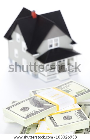 Real estate concept - bundles of dollars in front of house architectural model, isolated - stock photo