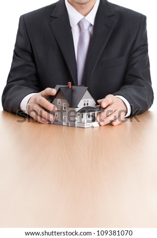 Real estate concept - businessman hands around home architectural model - stock photo