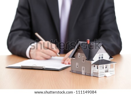 Real estate concept - businessman signs contract behind home architectural model - stock photo
