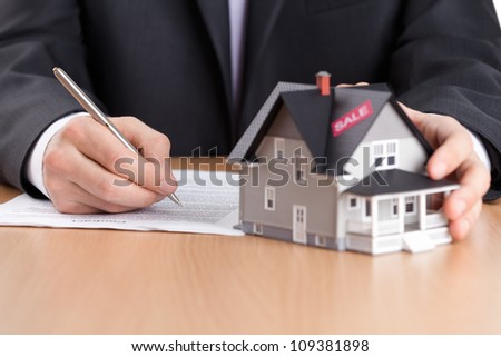 Real estate concept - businessman signs contract behind house architectural model - stock photo