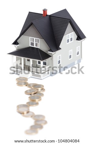 Real estate concept - coins in front of house architectural model, isolated - stock photo