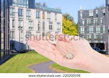 real estate concept - female hand with metal key over modern building - stock photo