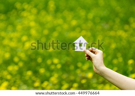 Real Estate Concept. Hand holding white paper house figure on blurred green background. Ecological building. Copy space. - stock photo