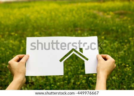 Real Estate Concept. Hand holding white paper house figure on blurred green background. Ecological building. Copy space.